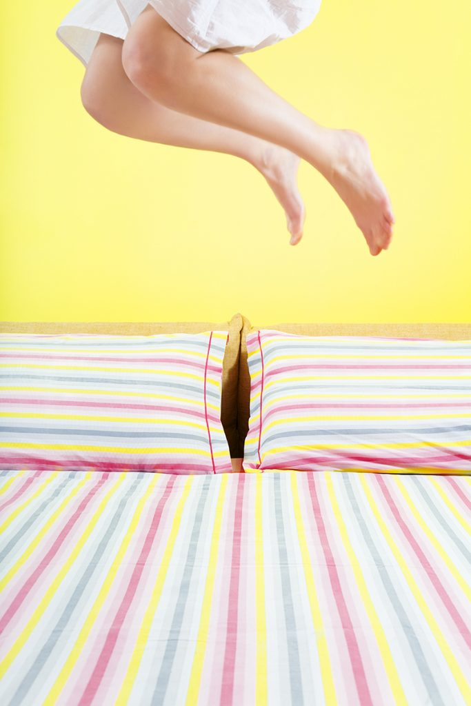 young woman jumping on bed with striped sheet