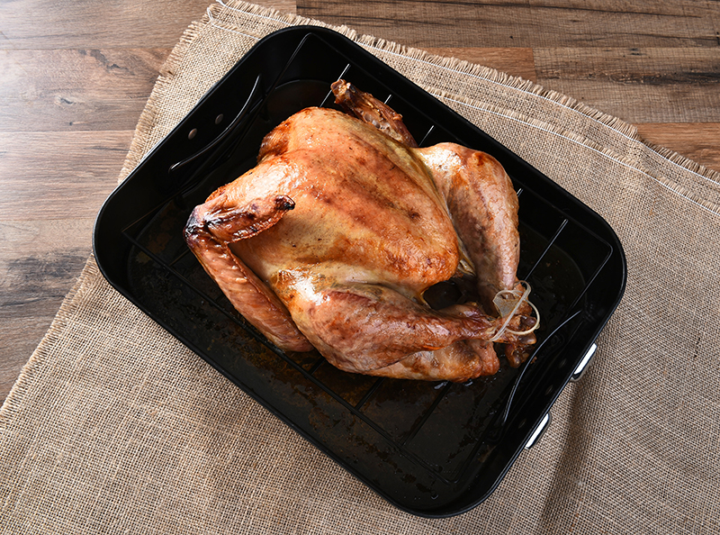 High angle view of a cooked turkey in a roasting pan. The golden brown Thanksgiving entree is in a black pan on a burlap table cloth.