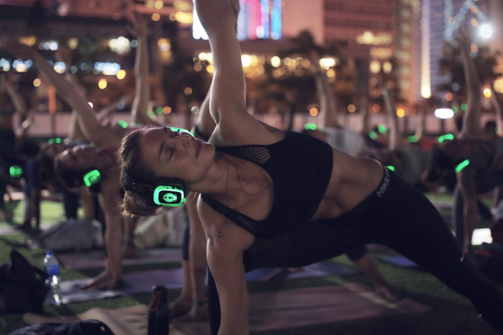 A woman practices yoga in a silent disco at IRIS Wellness Festival in Hong Kong