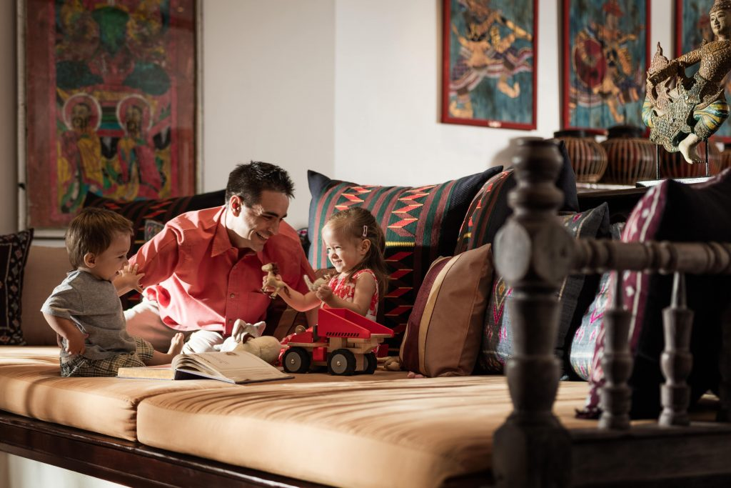 A man sits on a couch with his children while on holiday at Four Seasons Resort in Chiang Mai