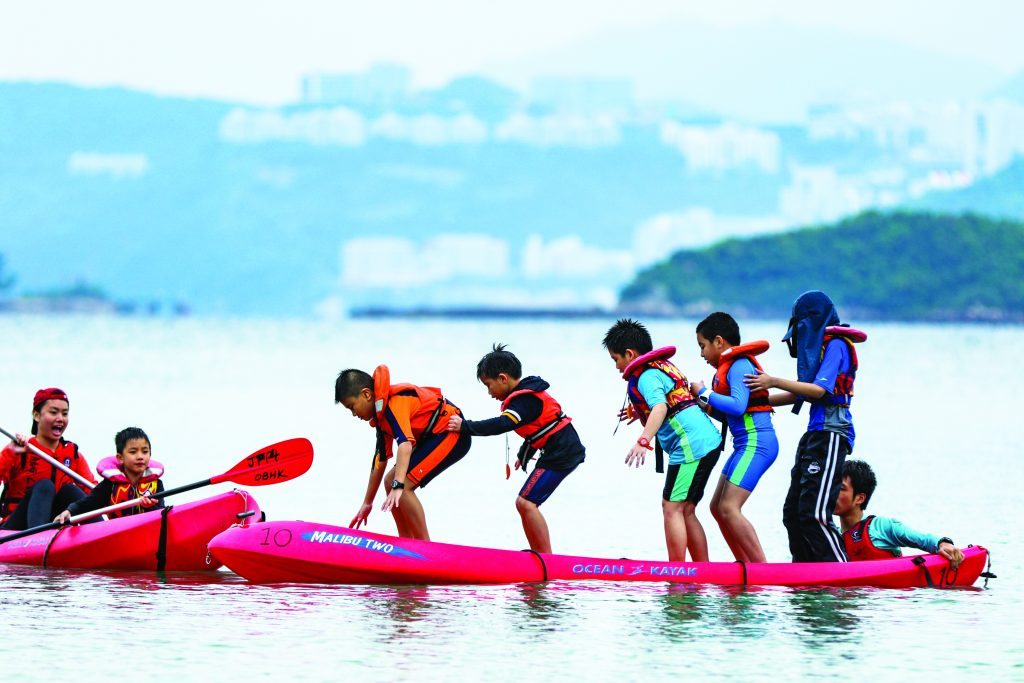 Several children stand on a kayak in the middle of the sea on an expedition organised by charity Outward Bound