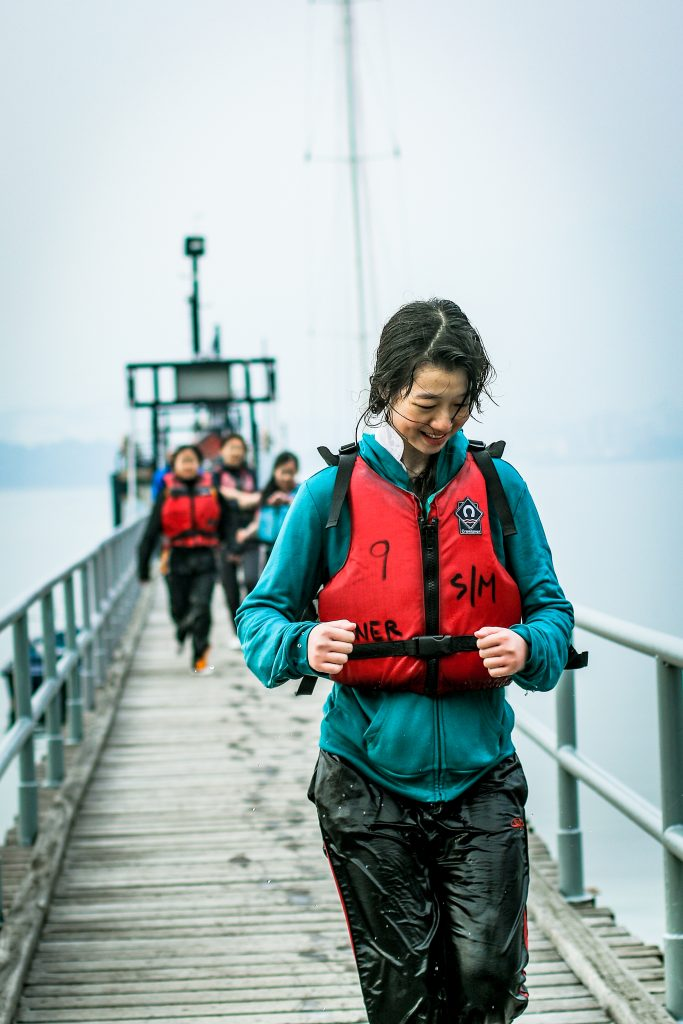 A woman runs with a life jacket on along a pier during an event with Outward Bound
