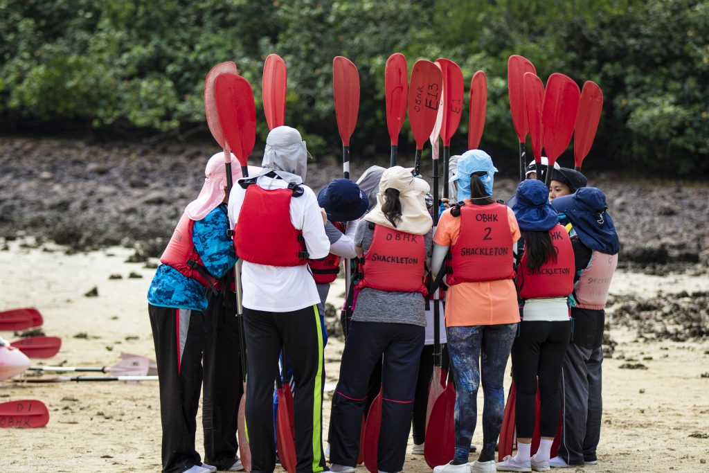 A group of young people stand on a beach with paddles in their hands in a group as part of a teamwork exercise.