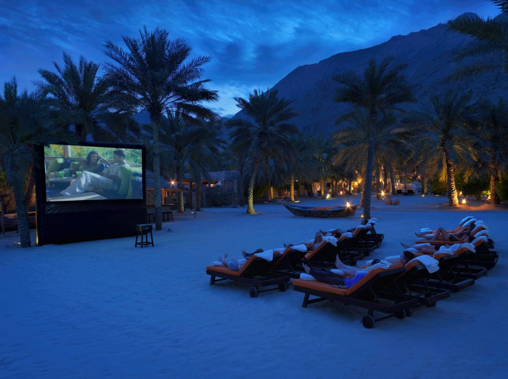 Several people watch a large outdoor television screen showing a film at the outdoor cinema at Six Senses Zighy Bay in Oman.