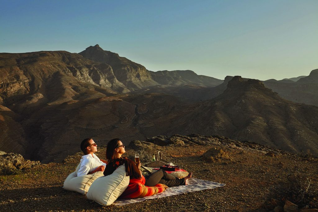 Two people sit on a blanket enjoying the view of Oman's countryside at Six Senses Zighy Bay resort.