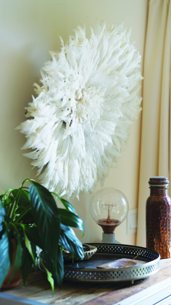 Decorative items, including a feather wall ornament and a copper water bottle.