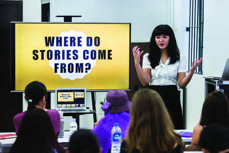 "A woman stands in front of a screen with the words ""Where do stories come from?"" on it, as part of the Hong Kong International Literary Festival"