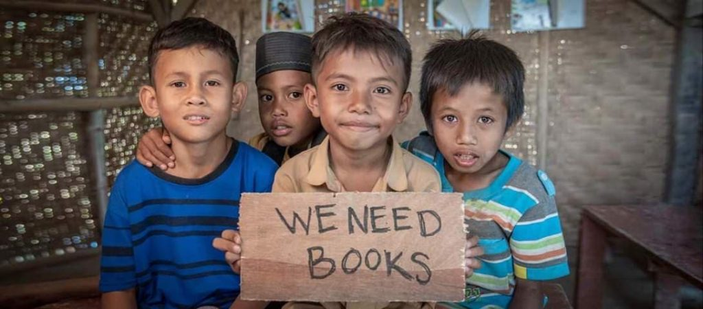 Four young children hold a sign asking for books, recipients of the Bloom Books charity from Lamma Book Club
