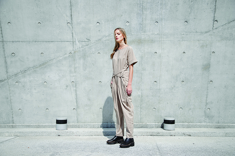 A woman in a beige jumpsuit made from sustainable materials.