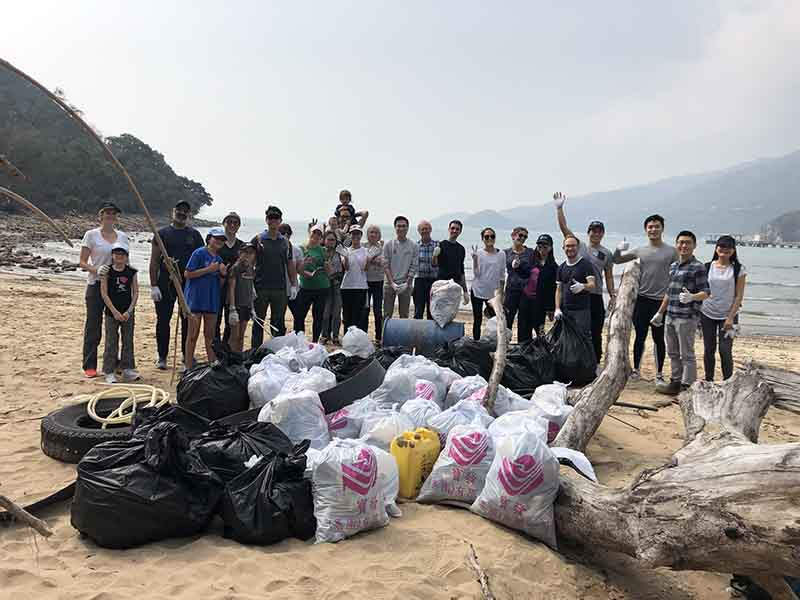 A group of people stand around a pile of collected rubbish on a beach in Hong Kong