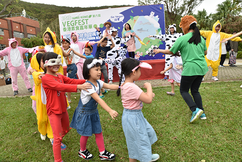 A group of children play in front of a banner for VegFest, a vegan festival in Hong Kong