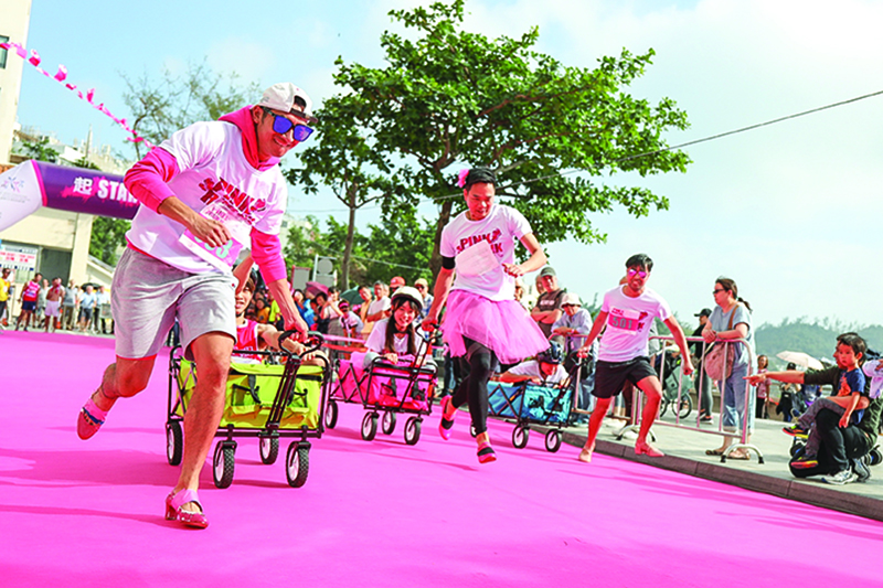 A group of men race down a pink carpet for the Pink Run wellness event in Hong Kong.