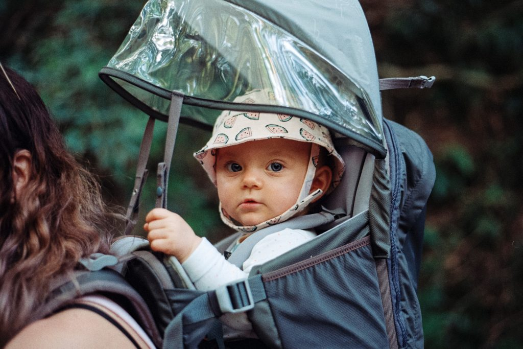 A  baby sits inside a baby carrier for hiking, covered with a rain cover.