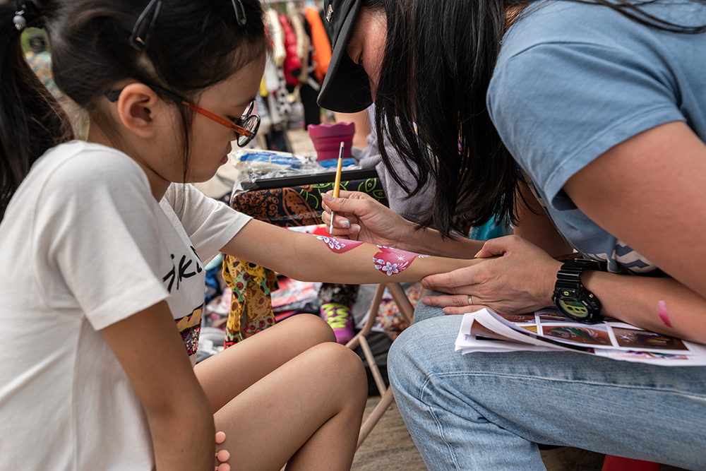 A girl has her arm painted at Lamma Fun Day, an annual wellness event in Hong Kong.