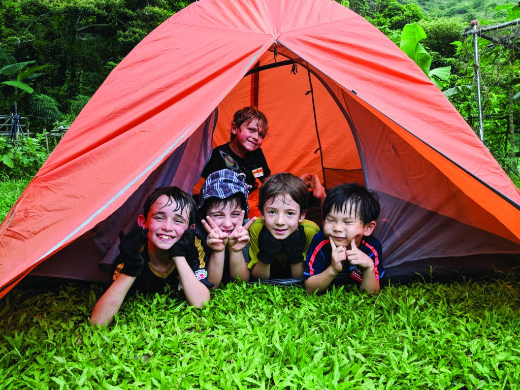A group of small children smile from inside a tent at Ark Eden, a family-friendly camping site in Hong Kong.