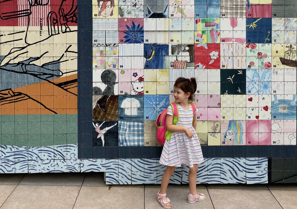 A small girl stands in front of an art installation at The Mills in Hong Kong.