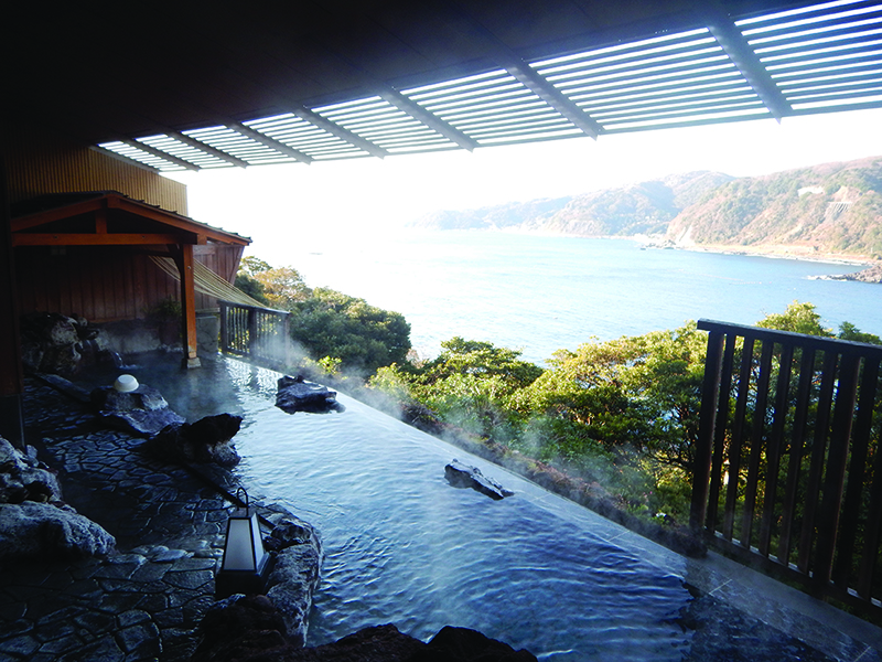 An onsen, or natural hot spring, with a view of the coastline. A popular wellness experience to try in Tokyo.