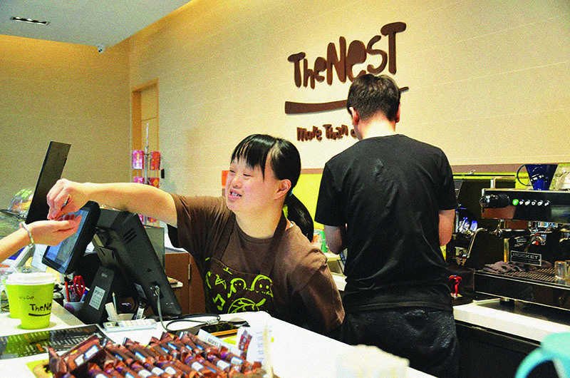 A woman with disabilities gives changes to a customer at social enterprise cafe run by charity The Nesbitt Centre in Hong Kong.