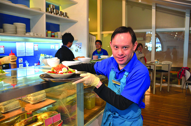 A man with disabilities holds a plate of food at a social enterprise cafe run by The Nesbitt Centre, a charity in Hong Kong.