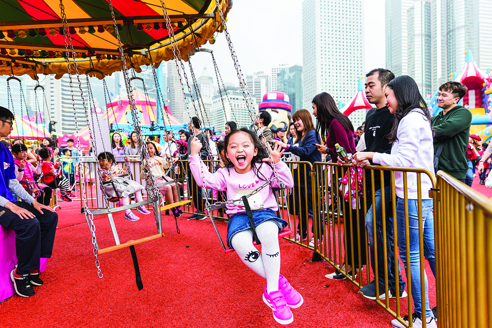 A girl on a ride at the AIA Carnival, a zero waste gift option for kids in Hong Kong.