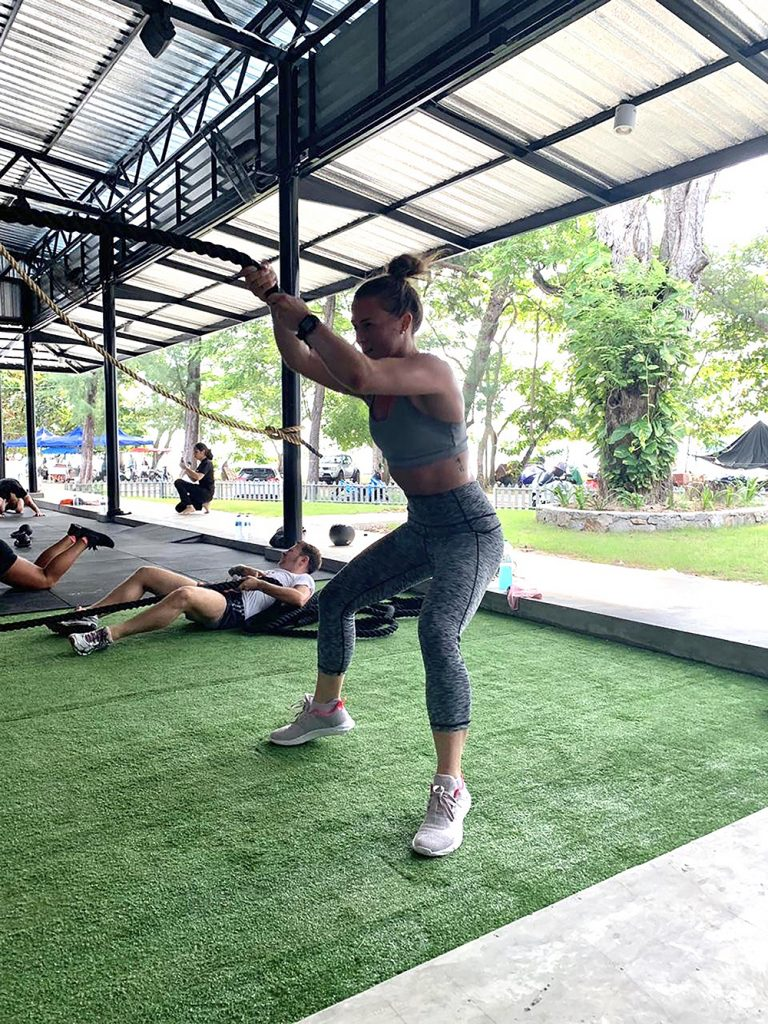 A woman works out strenuously in a gym, part of her self care routine.