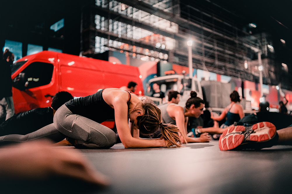 A woman stretches during a free workout class offered by Midnight Runners in Hong Kong.