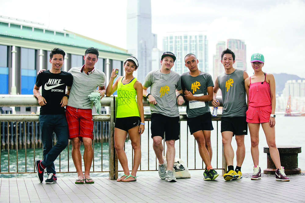 Several runners pose on Hong Kong's harbour, after a free workout class offered by Harbour Runners.