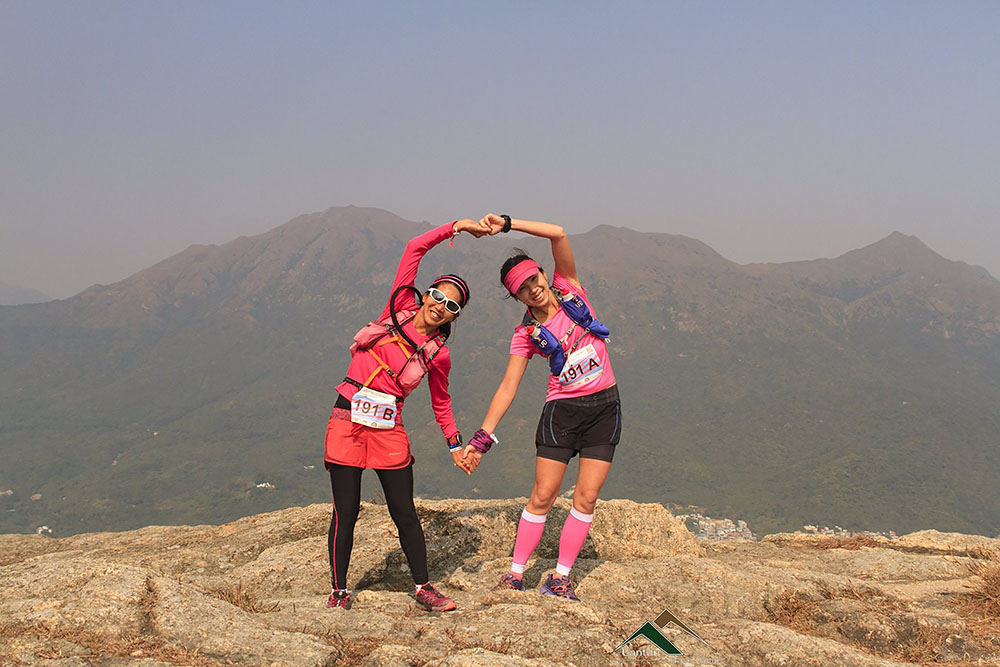 Two women make the shape of a heart on a mountain in Hong Kong during a Valentine's Day trail race, a wellness events in February.
