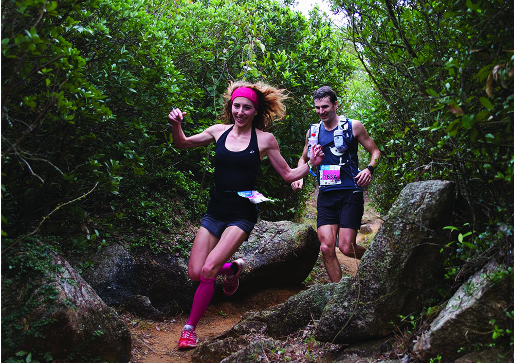 A woman and a man run on a trail during the Valentine's Day race, February wellness events in Hong Kong.