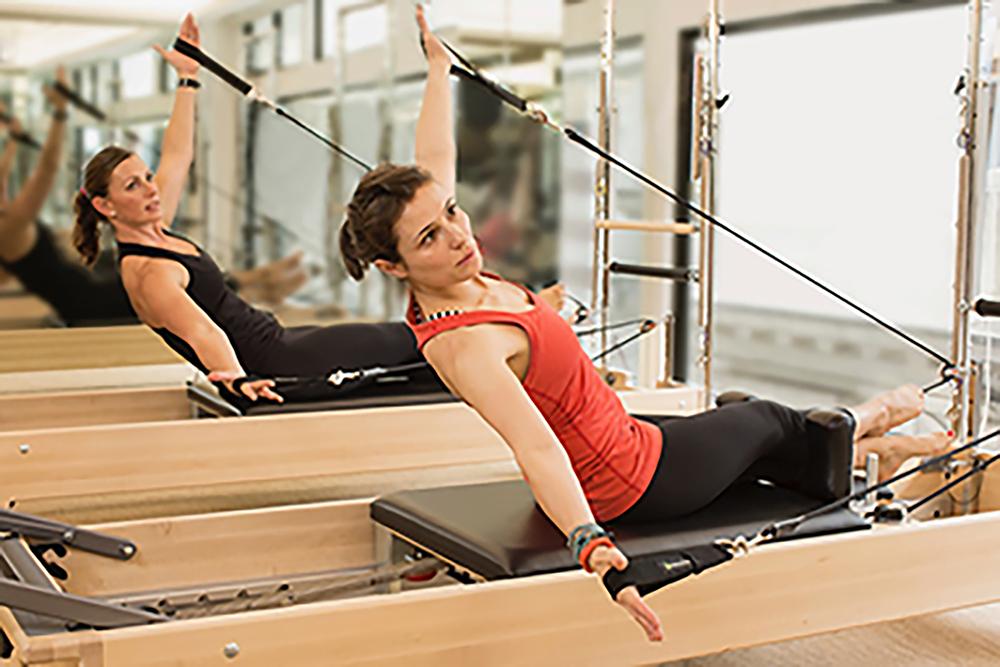 Two women use a Pilates Reformer machine at Flex, a participating partner in Wellness Week Hong Kong, a February wellness event.