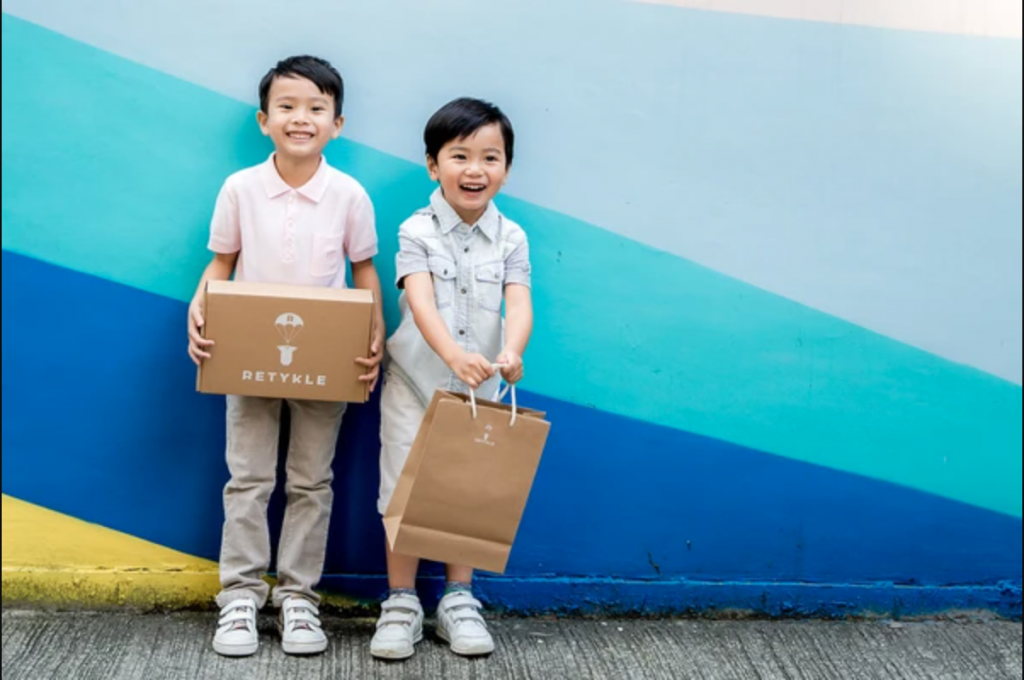 Two children hold Retykle bags, from a secondhand fashion shop in Hong Kong.