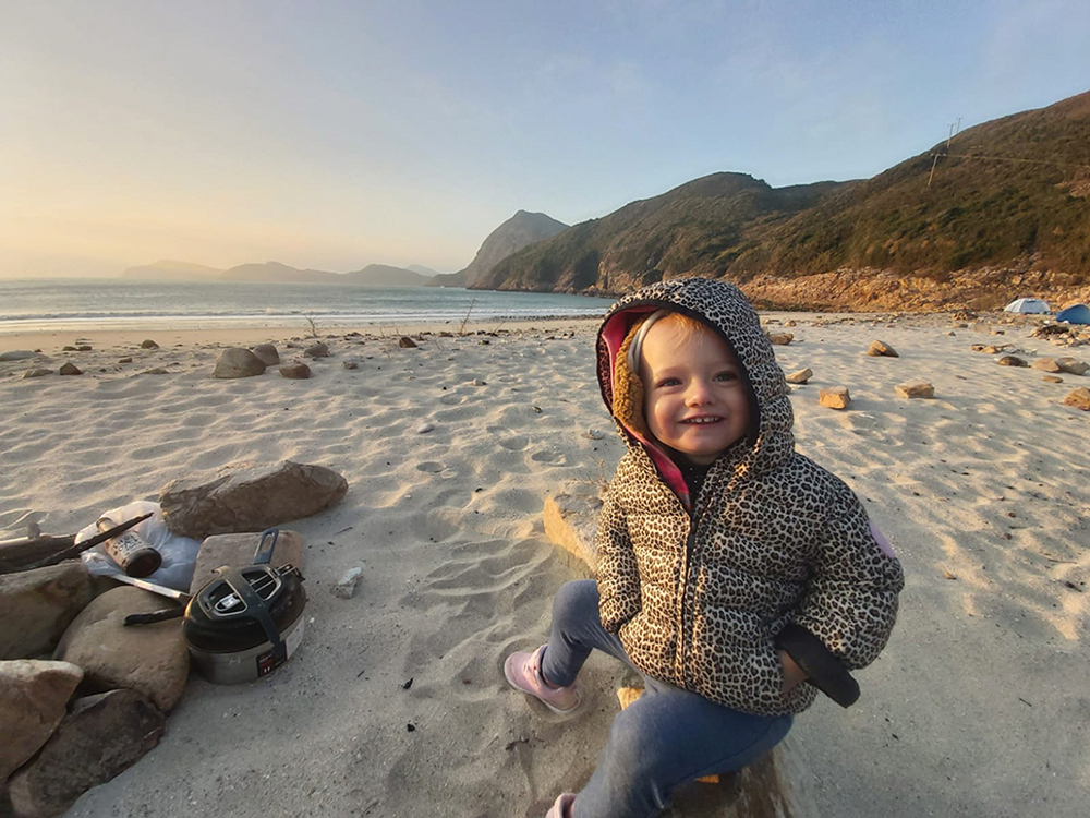 A young girl sitting on a beach at Pak Lap Wan, a family-friendly campsites in Hong Kong.