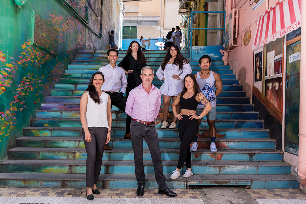 A group of seven people who are pandemic entrepreneurs stand on colourful steps in a Hong Kong neighbourhood.